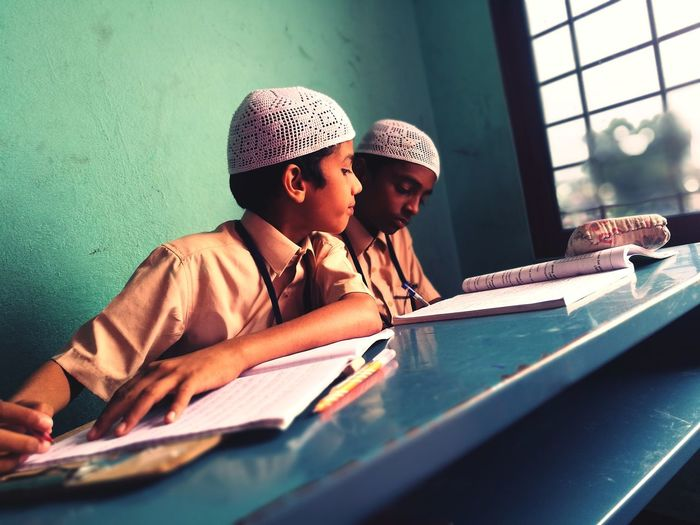 Close-up of students sitting on bench while studying at school