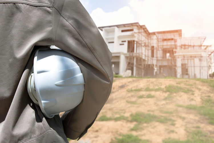 Midsection of engineer holding helmet