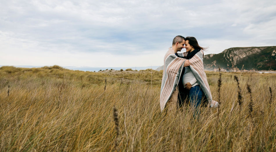 Pregnant woman with her husband embraced covered with a blanket on the field Autumn Couple Dad Family Field Happiness Horizontal Love Maternity Mother Motherhood Mum Romantic Waiting Young Belly Blanket Embracing Father Future Outdoors Pregnant Togheter Tummy Two People