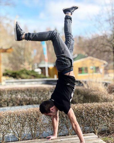 Full length of man doing handstand on table
