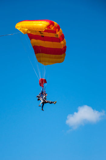 Adventure Blue Cloud - Sky Day Exhilaration Extreme Sports Flying Freedom Leisure Activity Low Angle View Mid-air Nature Outdoors Parachute Real People Sky Skydiving Sport Tandem Jump Transportation Two People Unrecognizable Person