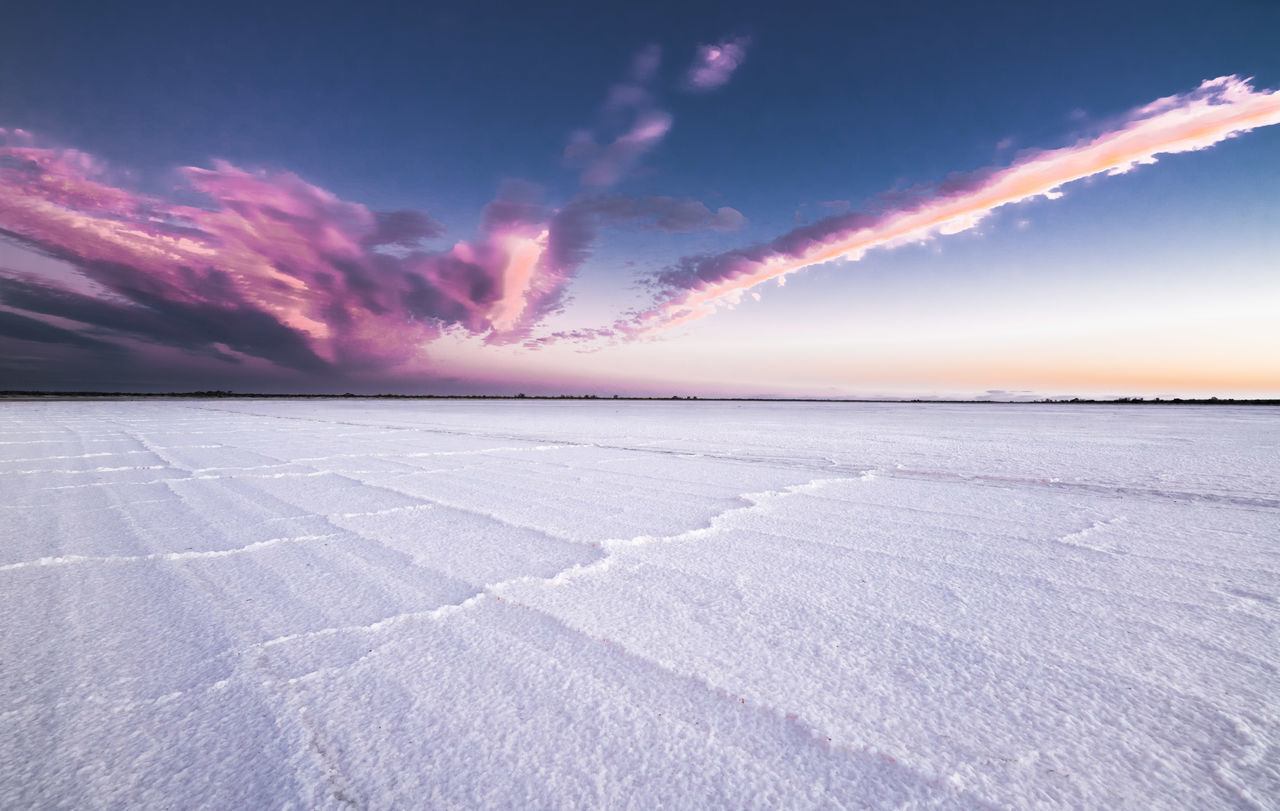 Scenic view of salt lake against sky during sunset