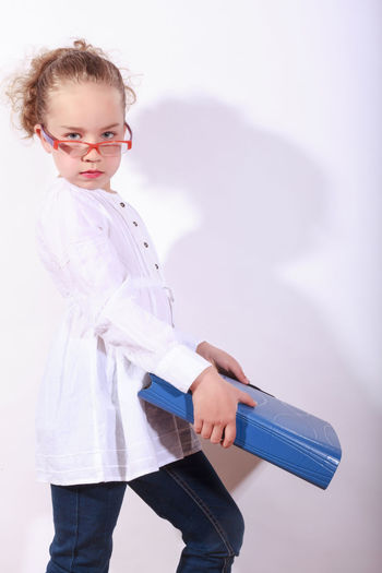 Portrait of girl with file standing against wall