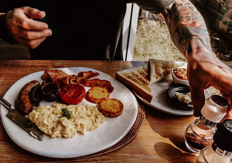 Close-Up Of Tattooed Man Enjoying Traditional English Breakfast