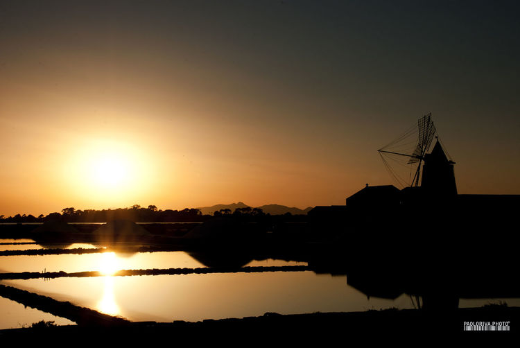 Architecture Beauty In Nature Bright Calm Clear Sky Dark Nature Orange Color Outdoors Reflection Sale Saline Scenics Silhouette Sky Sun Sunbeam Sunset Tranquil Scene Tranquility Water Waterfront Windmill
