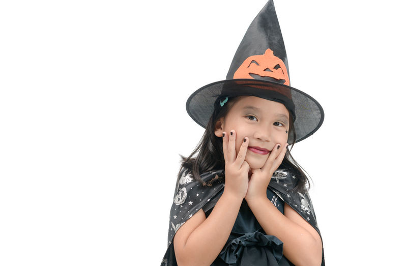 Portrait Of Girl Wearing Witch Costume Against White Background
