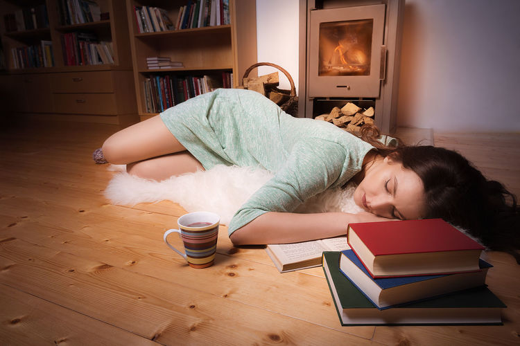 Young woman sleeping by books at home