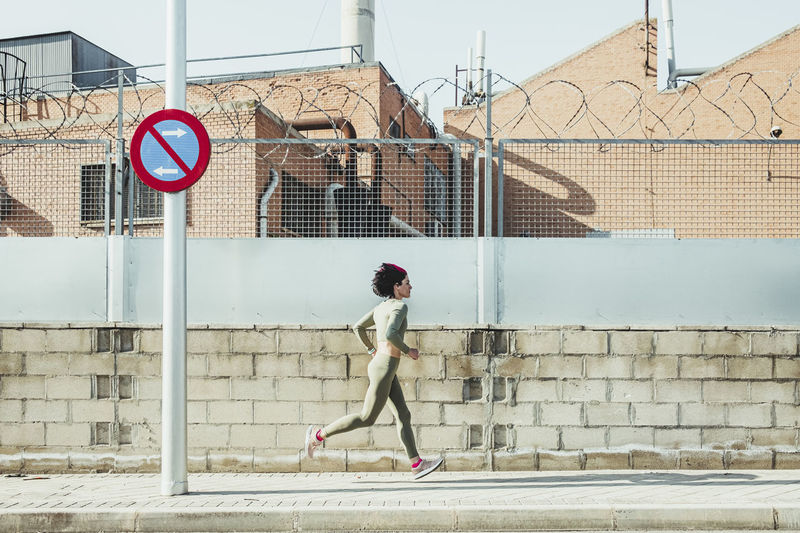 Full length of woman on road against wall