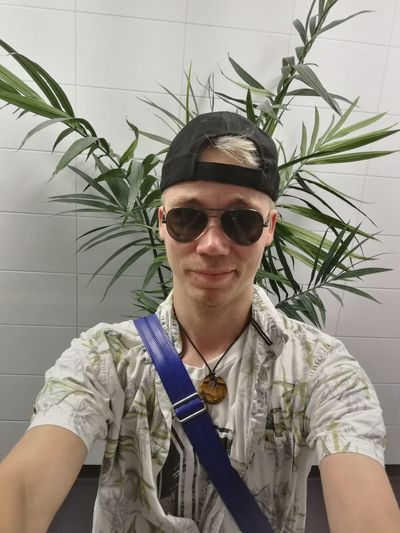 Portrait Of Young Man Wearing Sunglasses While Standing Against Plant