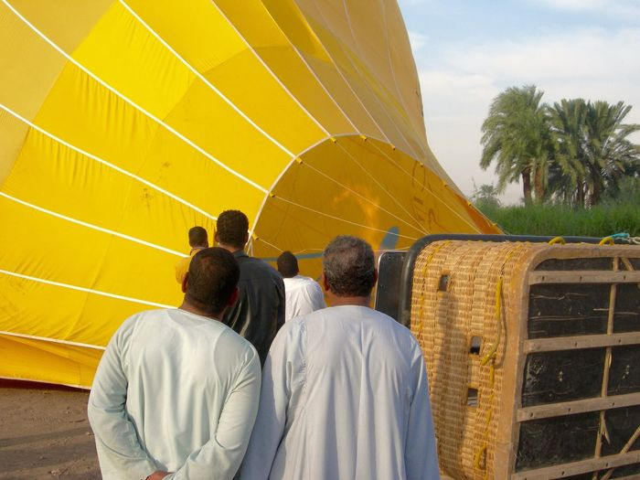 Rear view of people by hot air balloon against sky