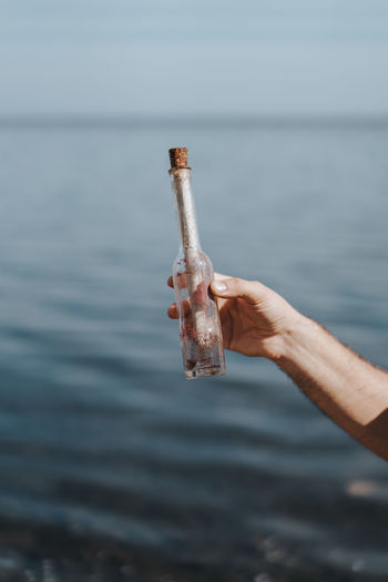 Person holding message in the bottle at sea shore