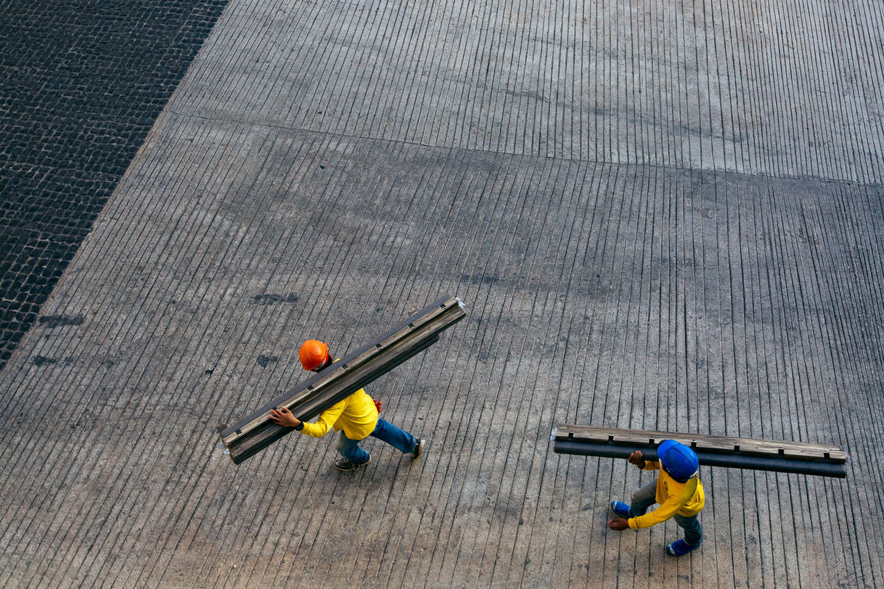 High angle view of workers carrying girder on street