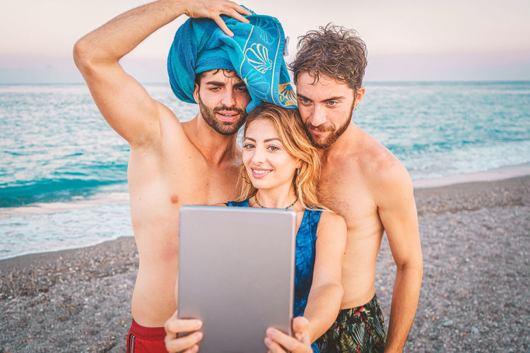 Portrait of young man using mobile tablet device at beach