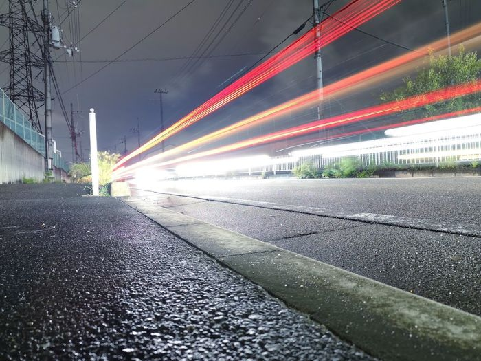 Light trails on road by train in city