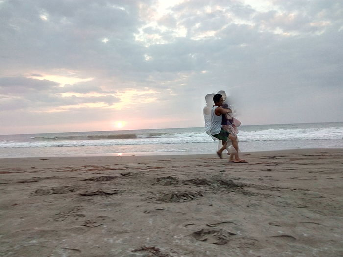 Blurred motion of couple embracing at beach against cloudy sky