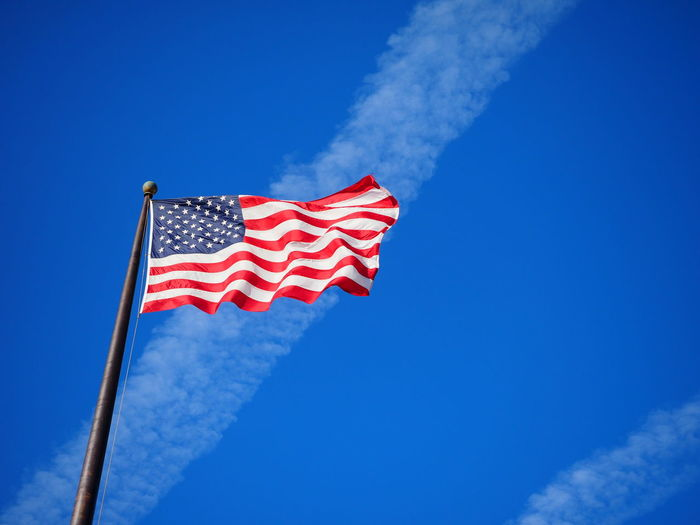 The American flag flies on a clear sunny day. American American Flag Cloud USA USA FLAG America Blue Clouds And Sky Day Flag Freedom Independence Low Angle View National Icon No People Outdoors Patriotism Pole Red Sky Star Shape Stars And Stripes Striped Waving Wind
