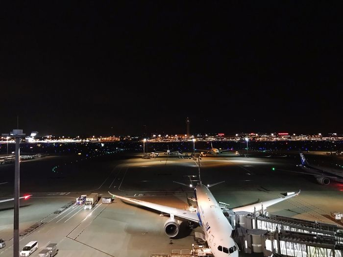 High angle view of illuminated airport runway against sky at night
