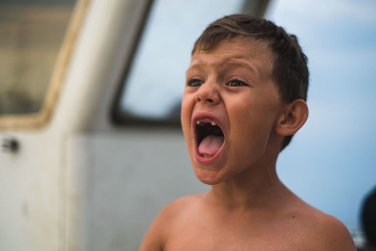 Close-Up Of Shirtless Boy Screaming While Standing At Beach