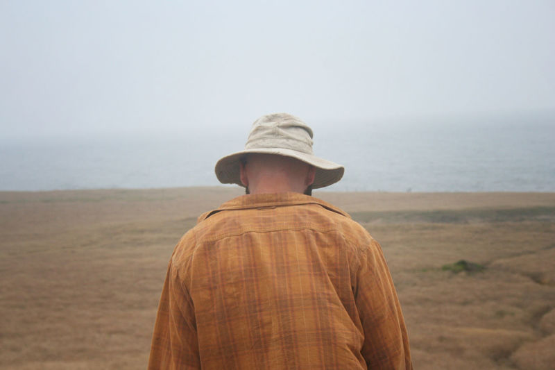 Walking to the shore, rear view of man in casual clothing and hat on a misty morning Mendocino County Misty Casual Clothing Clothing Day Hat Headlands Horizon Land Leisure Activity Men Misty Morning Nature One Person Outdoors Pacific Coast Real People Rear View Sea Sky Waist Up Water
