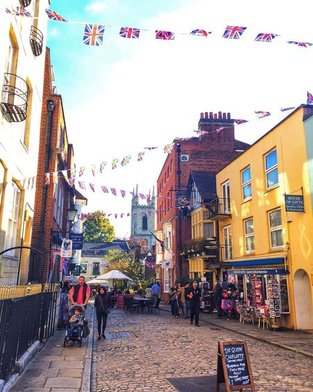 English town Eye4photography  EyeEm Gallery Yellow Union Jack Flags Building Exterior Architecture Built Structure City Sky Street Building Clear Sky Incidental People Decoration Crowd Day