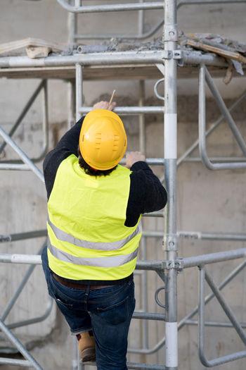 Construction worker climbing on scaffolding