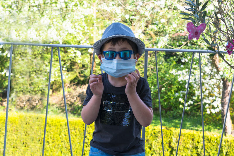 Portrait of boy wearing surgical mask while standing against railing
