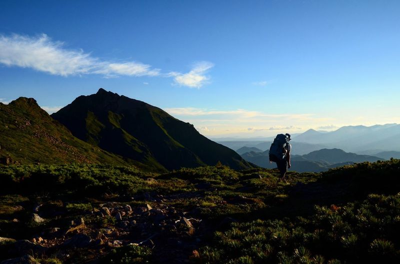 Man hiking on mountain against sky