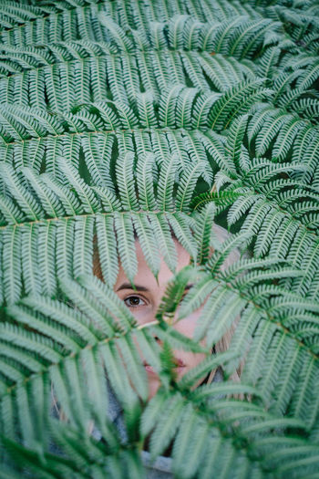 Close-Up Portrait Of Woman Looking Through Tree