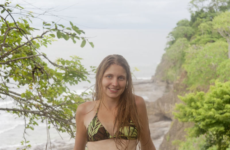Portrait of young woman wearing bikini standing against sea at island