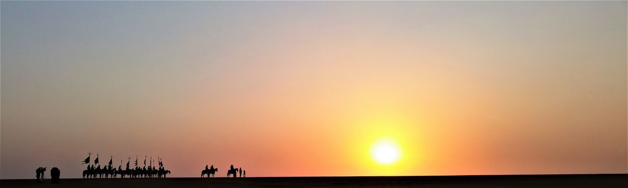 Panoramic view of silhouette people with domestic animals standing on field against sky during sunset