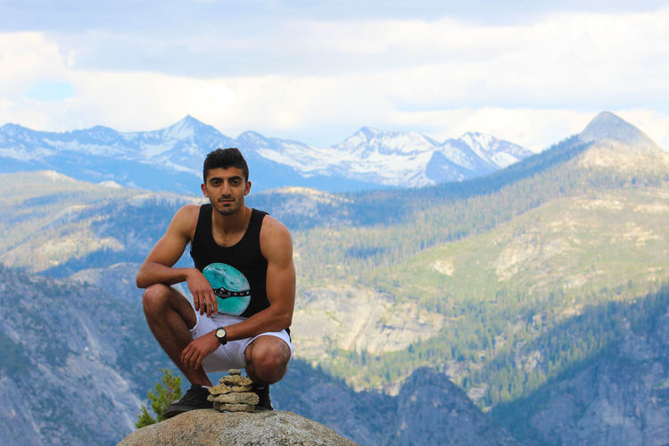 Portrait of young man crouching on cliff with mountains in background