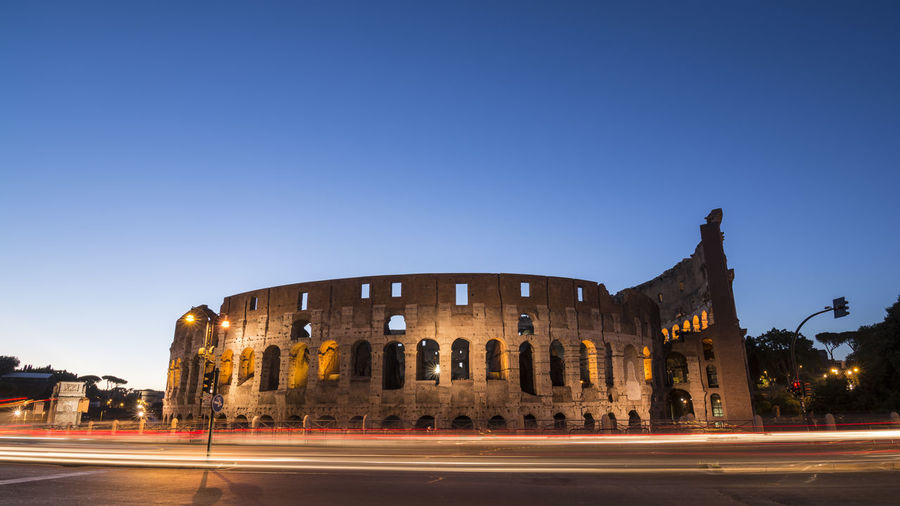 Low angle view of coliseum against sky at night