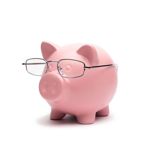 Close-Up Of Piggy Bank With Eyeglasses On White Background