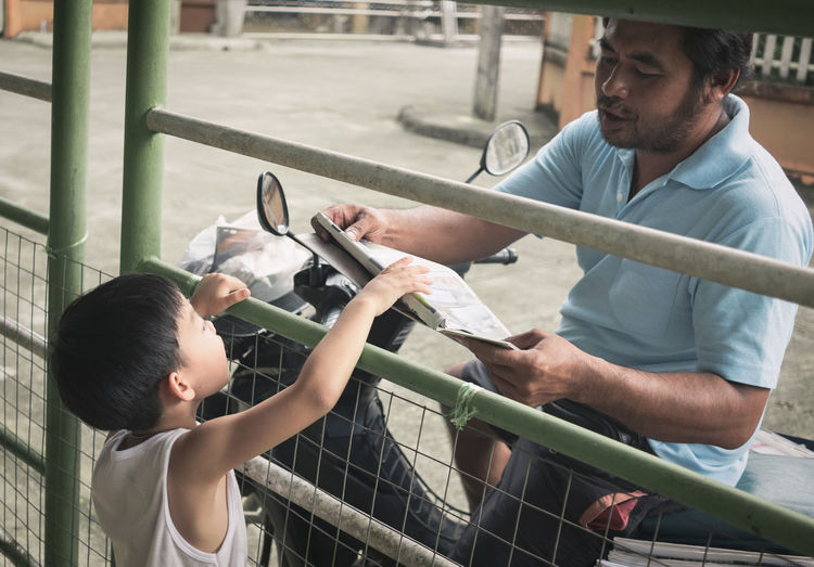 Boy receiving newspaper from delivery man while standing at gate