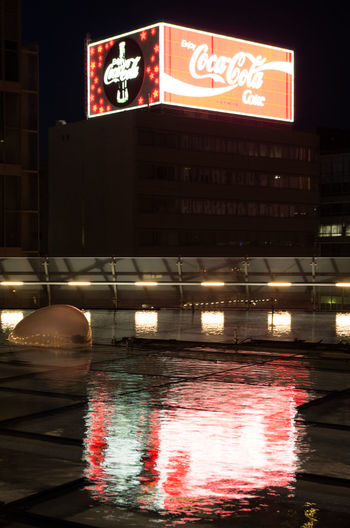 Reflection of illuminated text on water in city at night