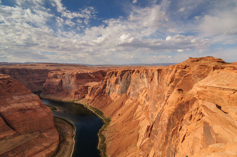 Colorado River Amidst Rock Formations At Horseshoe Bend Against Sky