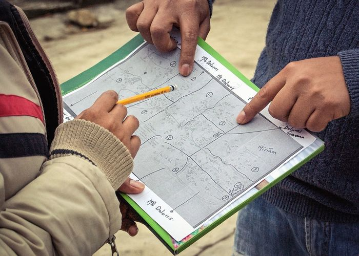 Growing Better - For humanitarian aide organizations, assessing impact and improvement is essential. Here two household survey workers go over a map of a rural community in the mountains of Mexico. The map is handmade and homes plotted out from memory. They walked from home to home asking to interview people until they have reached their quotas. Typically it takes close to 12 hours to complete a days work. Mexico Nonprofit NGO Map