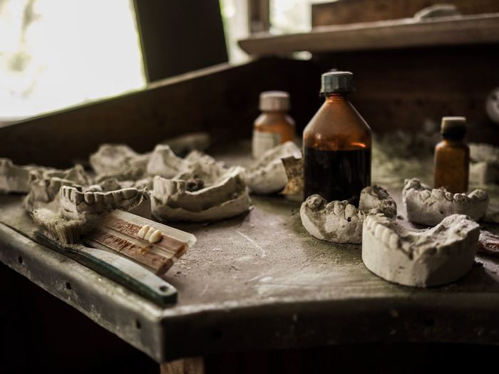 Close-up of dentures and bottles on table