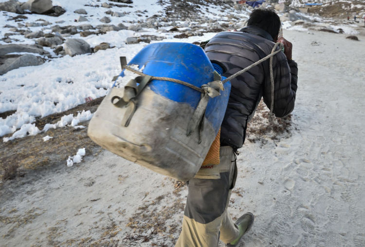 Rear view of man carrying plastic can while walking on snow covered field