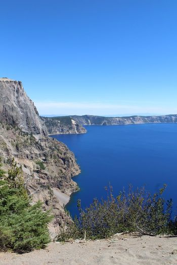 Beauty In Nature Blue Clear Sky Cliff Coastline Crater Lake Crater Lake National Park Day High Angle View Mountain Nature Non-urban Scene Outdoors Remote Rock Formation Scenics Solitude Tranquil Scene Tranquility Vacations Water