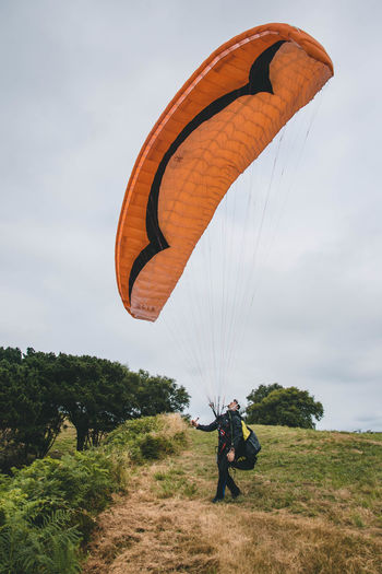 Person paragliding over field against sky