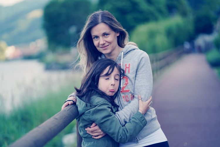 Portrait Of Mother With Daughter Standing On Bridge