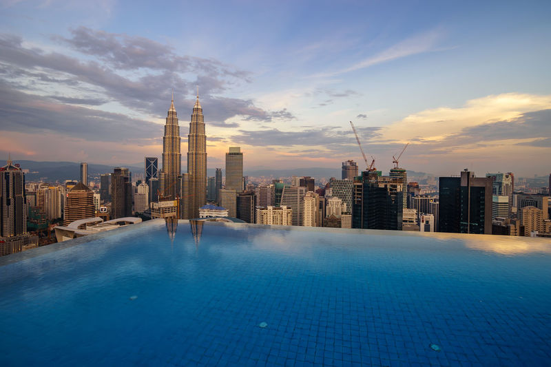 Infinity Pool Against Petronas Towers During Sunset In City