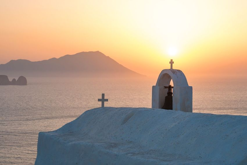 Summer sunset in Milos, Greece with a whitewashed Greek Orthodox chapel in the foreground and Antimilos in the Aegean Sea in the background. Religion Sunset Sea Nature Tranquil Scene Spirituality Whitewashed Beauty In Nature Tranquility Water Scenics Cross No People Sky Sunlight Outdoors Built Structure Horizon Over Water(null) Travel Destinations Greek Islands Milos Island EyeEmNewHere Aegean Sea Serene