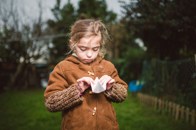 Girl making origami while standing on land