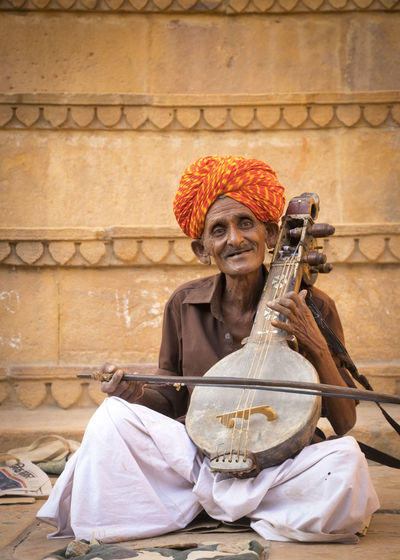 the unknown musician India Musician Traditional Fort Rajasthan Colour Street Orange Heritage Jaisalmer Culture EyeEm Selects Manual Worker Working Sitting Business Women Portrait Looking At Camera Cultures Occupation Happiness Street Scene