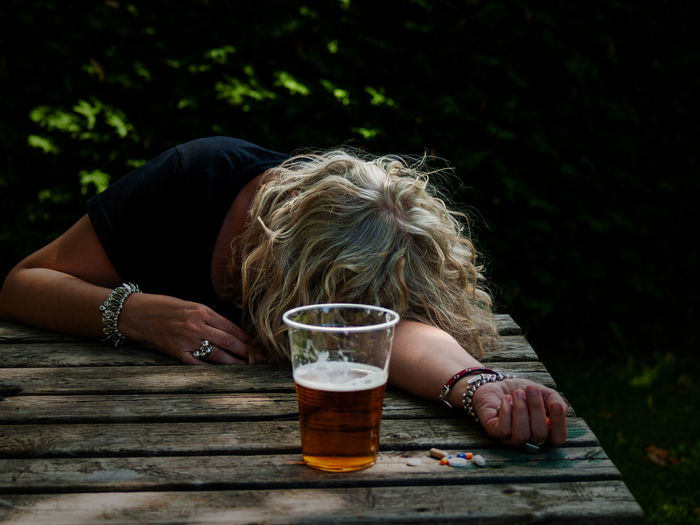 Woman drinking beer while holding pills on table