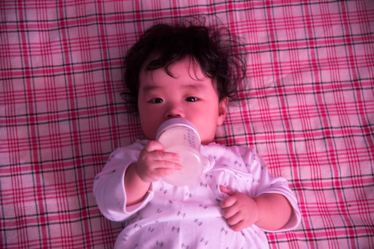 Close-up portrait of cute baby holding milk bottle while lying on blanket