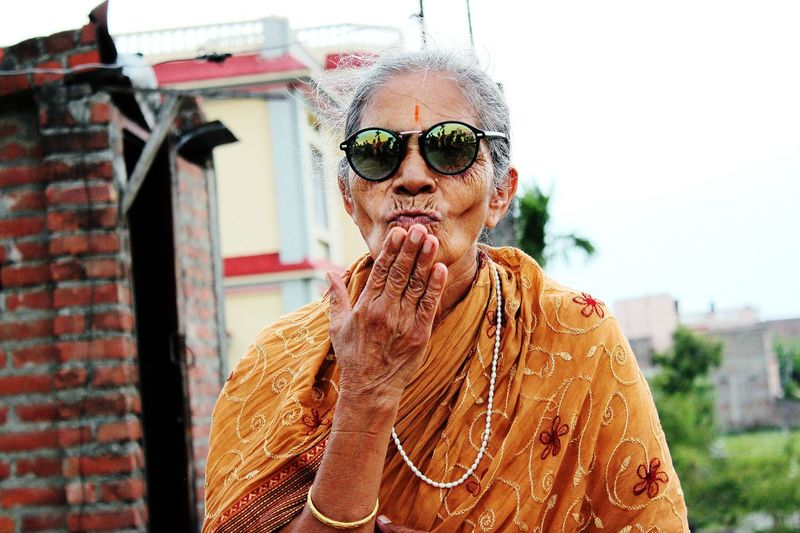 Senior Woman Wearing Sunglasses Blowing Kiss