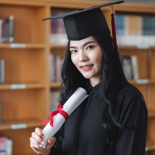 Portrait of student holding degree while standing against shelf